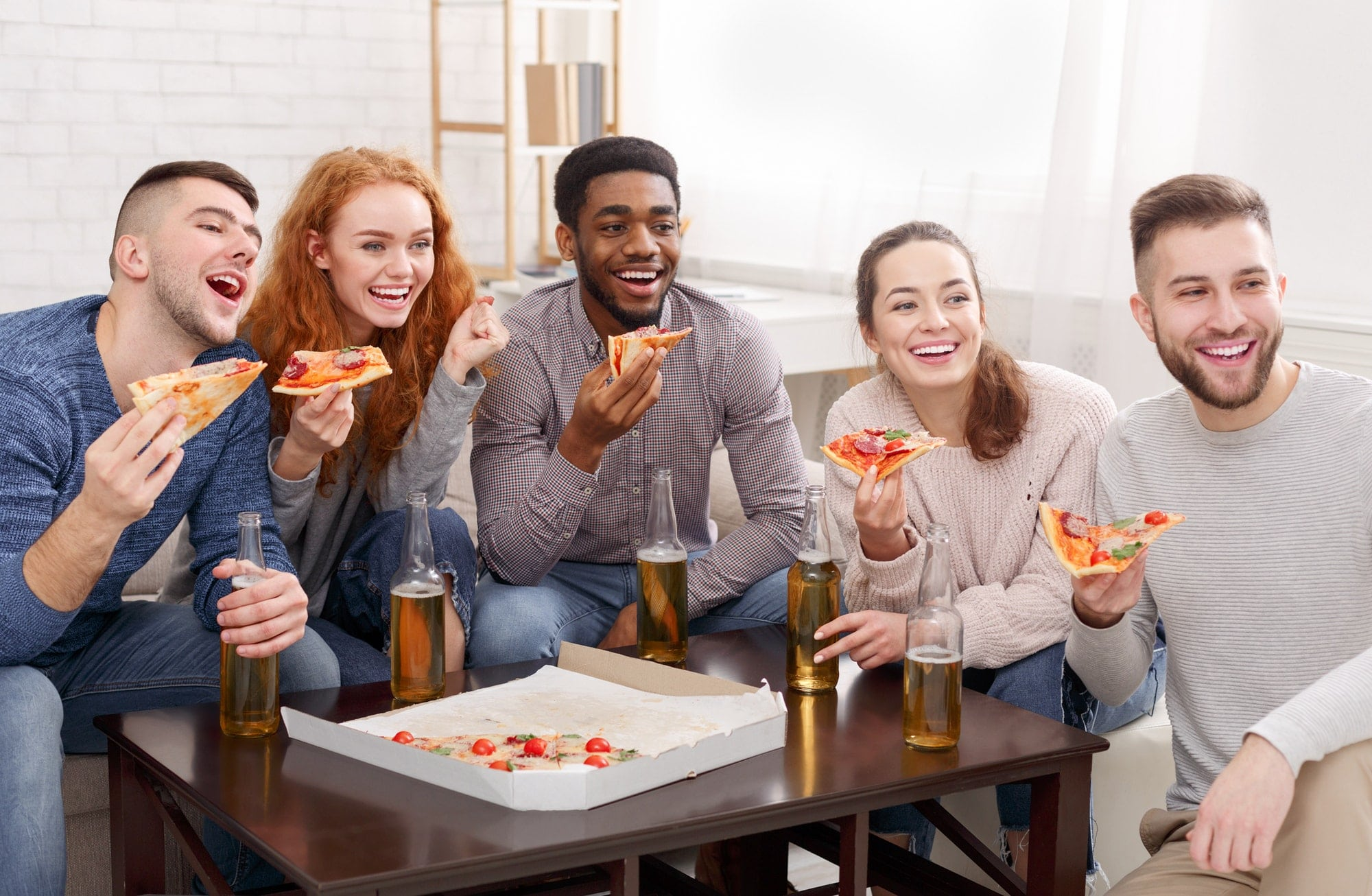 Friends eating pizza and watching comedy film